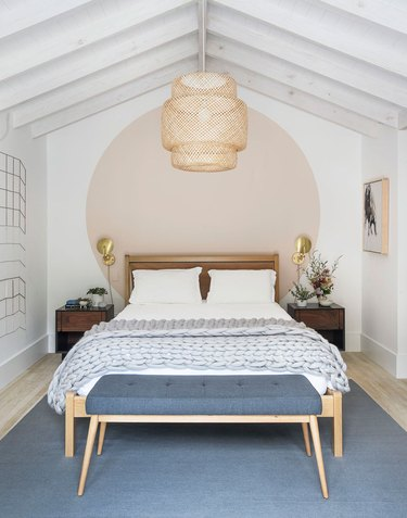 bedroom with pink circle accent wall and Ikea pendant