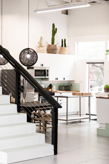 Black and white painted stair rails leading to minimalist kitchen.
