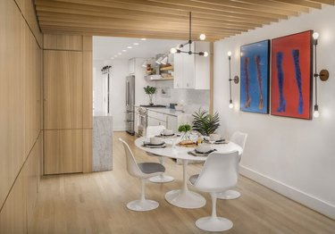 basement ideas with Modern white round dining table with matching chairs, modern red and blue artwork, light paneled walls, light wood floors, basement apartment.