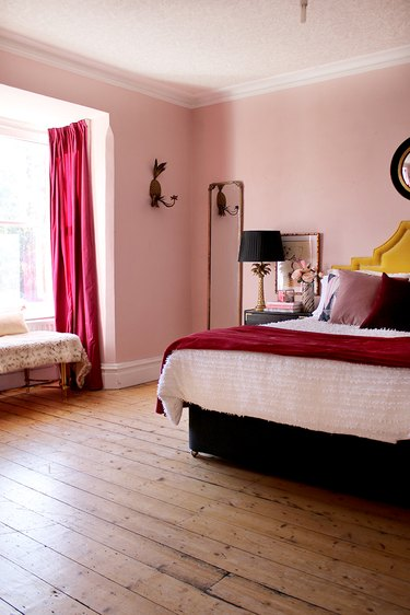 pink bedroom with dark pink drapery and bedding and wood flooring