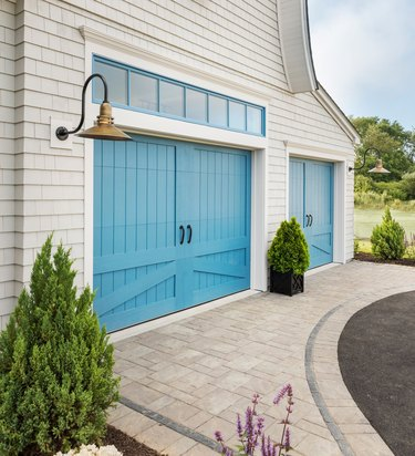 Exterior Garage Lighting on white farmhouse exterior with brass bell style pendant