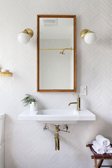 thin wall-mounted bathroom sink on herringbone wall tile and brass fixtures