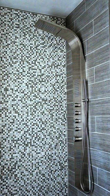 Shower panel with handheld shower head and body sprays with contemporary tiled shower wall