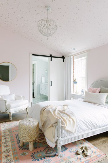 pale pink bedroom with area rug and barn style door