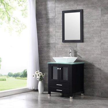 glass bathroom countertop with white vessel sink near window