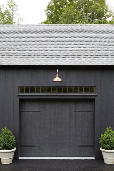 modern black exterior with brass exterior garage lighting