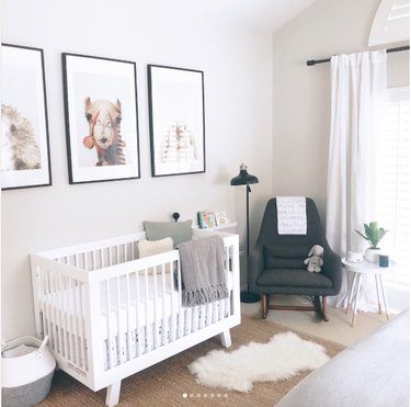 Gender-neutral nursery with three large photo prints of animal heads on wall: camel, hedgehog, and bunny; gray midcentury rocking chair, and white convertible crib