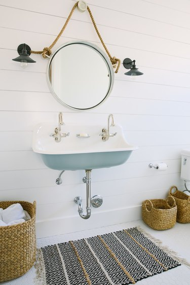white bathroom with shiplap walls and blue trough sink