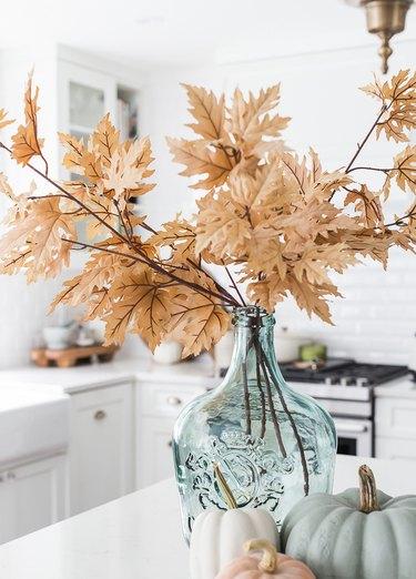 coastal fall decor with turquoise glass vase and foliage