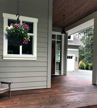 gray exterior paint with stained porch and hanging flowers