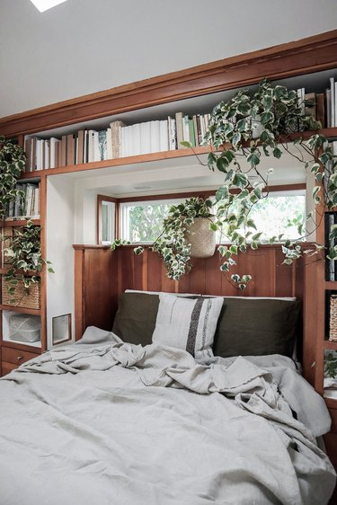 small bedroom with built-in shelving and greenery
