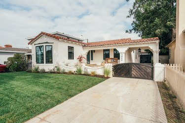 White home with Spanish-style roof, green grass lawn, concrete driveway with wooden gate