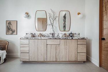 contemporary bathroom with marble countertop and light wood vanity cabinet