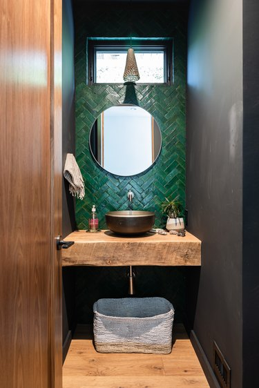 Small bathroom with wood counter and sink, with green tile backsplash and hanging ceramic pendant light.
