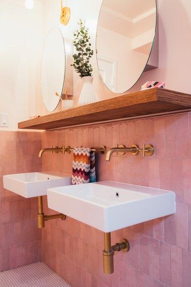 Pink tiled bathroom with wood shelf