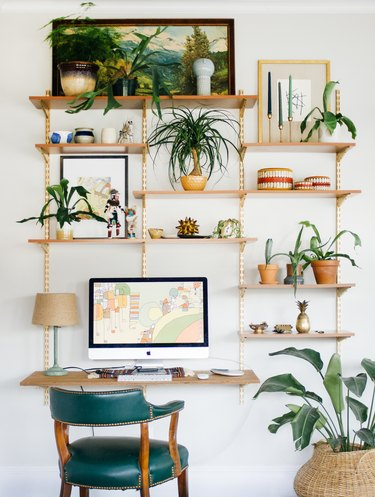 small home office with wall-mounted shelving and green desk chair