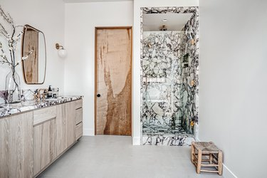 Black and white marble shower with wood and marble sink in bathroom