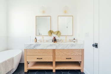 Bathroom with square brass mirrors, sconces, wood and marble sink, and tub