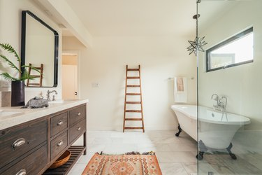 A spacious bathroom with a wood vanity with double sinks, a freestanding clawfoot tub, a glass shower door, a colorful rug, a decorative ladder leaning against the wall