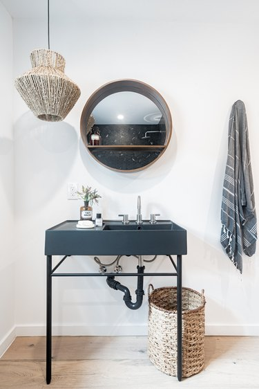 Bathroom with black sink, circle mirror, rattan pendant lamp, and basket