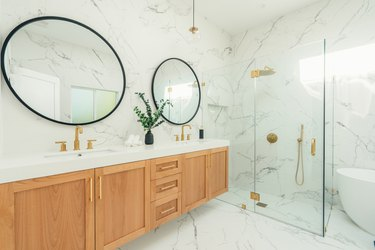 Bathroom with marble floor and walls, wood sink area, glass shower, large round mirrors