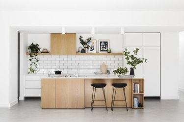 white subway tile kitchen backsplash with wood cabinets and white countertop