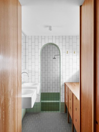 alcove type of shower with white and green tiles