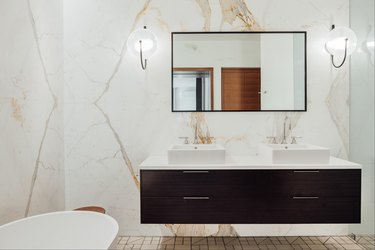 solid surface bathroom countertop with dark wood vanity and marble accent walls
