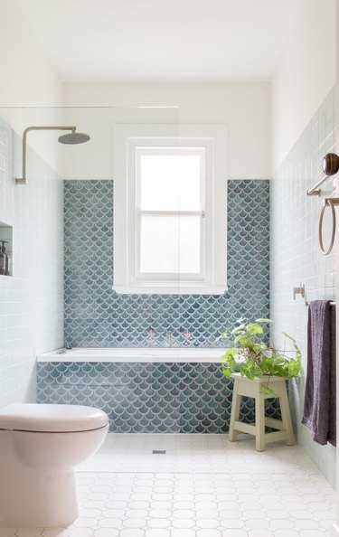 wet room with shower and small bathtub covered in blue fishscale wall tile