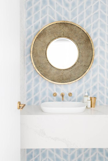 vessel bathroom sink on marble countertop with patterned wallpaper