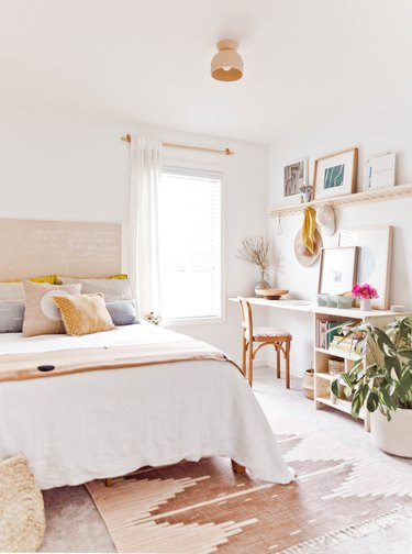 small home office in a guest bedroom near window with potted plant