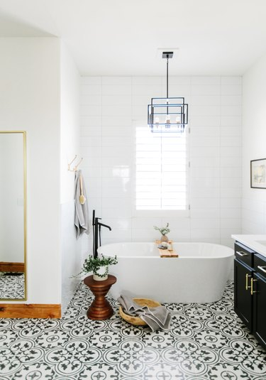 modern bathroom with small bathtub and patterned floor tile