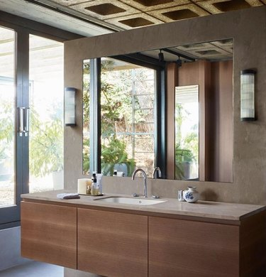 solid surface bathroom countertop with floating wood vanity and large frameless mirror