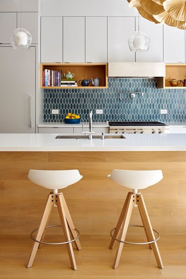 midcentury modern kitchen backsplash idea with blue tile and white cabinets