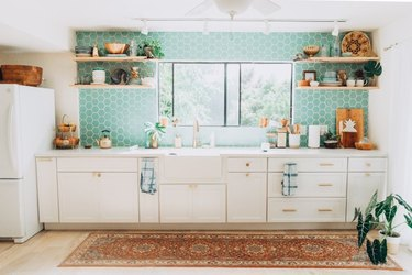 hexagon aqua tile in modern kitchen with white cabinets and farmhouse sink and area rug on floor