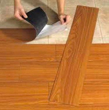 Installing self-stick tiles.