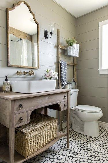 vessel bathroom sink on rustic wood vanity with shiplap walls and patterned floor tile
