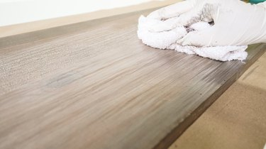 Blending whitewash with rag for faux weathered wood finish.