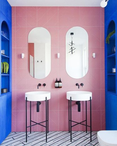 modern bathroom lighting with pink and blue walls and console sinks