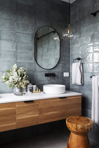 modern bathroom lighting with globe style pendant at vanity with blue wall tile