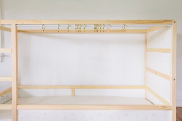 Tension rod and curtain rings hung across KURA bed