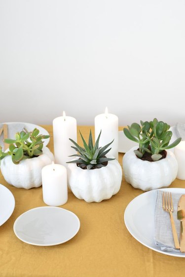 all-white pumpkin planters with white candles on a tabletop with place settings