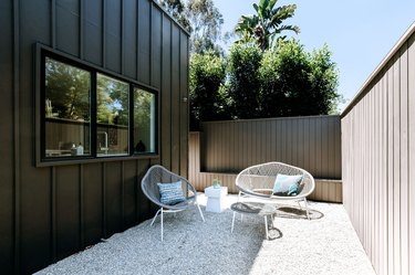 a side yard of a modern home with a pea gravel patio, white mid-century modern patio furniture