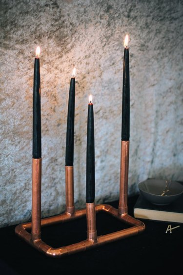 copper candelabra with four black tapered candles