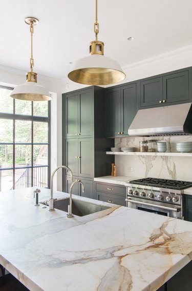modern kitchen with dark green cabinets and marble countertops