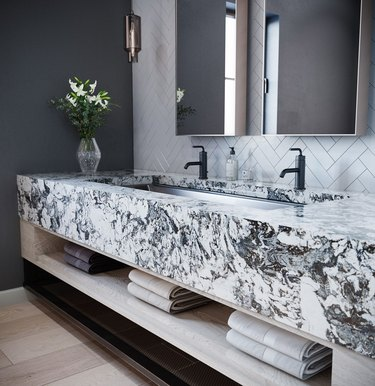 thick slab quartz bathroom countertop with black faucets and chevron wall tile