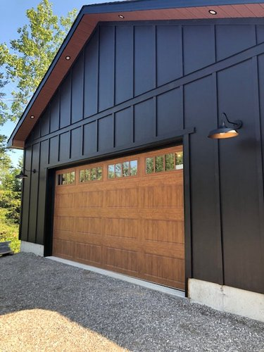 black home exterior with wood garage door and sconces