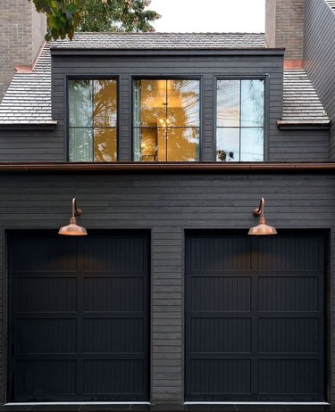 black home exterior with two garage doors and copper wall sconces
