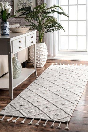 trellis rug near dresser and plant