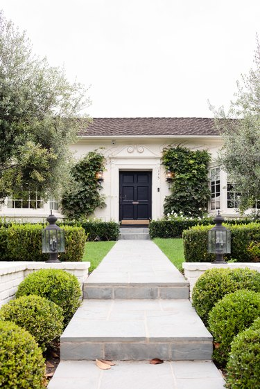 a regal white house with black door, a long concrete path with evenly spaced green hedges that are well manicured
